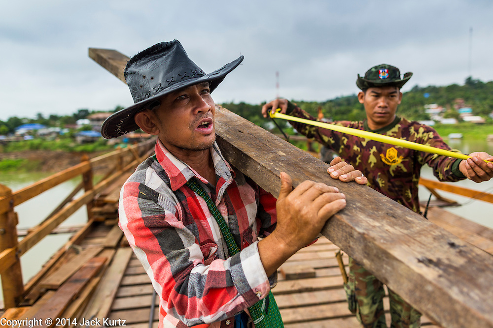 16 SEPTEMBER 2014 - SANGKHLA BURI, KANCHANABURI, THAILAND: A member of the Mon community and a Thai soldier carry a piece of lumber to the work area on the Mon Bridge. The 2800 foot long (850 meters) Saphan Mon (Mon Bridge) spans the Song Kalia River. It is reportedly second longest wooden bridge in the world. The bridge was severely damaged during heavy rainfall in July 2013 when its 230 foot middle section  (70 meters) collapsed during flooding. Officially known as Uttamanusorn Bridge, the bridge has been used by people in Sangkhla Buri (also known as Sangkhlaburi) for 20 years. The bridge was was conceived by Luang Pho Uttama, the late abbot of of Wat Wang Wiwekaram, and was built by hand by Mon refugees from Myanmar (then Burma). The wooden bridge is one of the leading tourist attractions in Kanchanaburi province. The loss of the bridge has hurt the economy of the Mon community opposite Sangkhla Buri. The repair has taken far longer than expected. Thai Prime Minister General Prayuth Chan-ocha ordered an engineer unit of the Royal Thai Army to help the local Mon population repair the bridge. Local people said they hope the bridge is repaired by the end November, which is when the tourist season starts.    PHOTO BY JACK KURTZ
