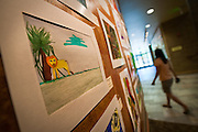A patron of the Coeur d'Alene Public Library walks past the new children's art display nearby the children's section on the lower level of the facility on Thursday.