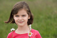 Girl (7-9) wearing ring of flowers in meadow portrait