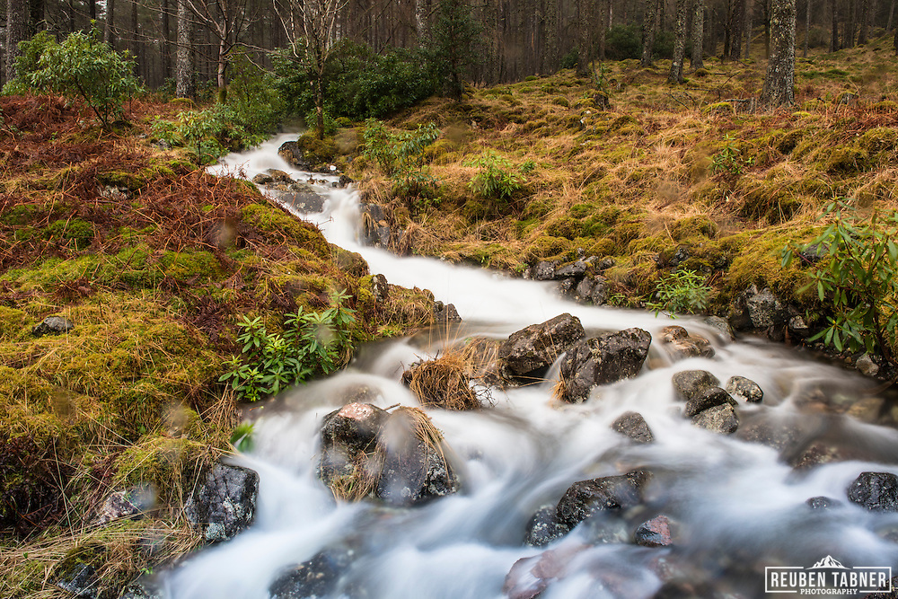 A stream in full spate flows down the hill side in Glen Etiv, in the Highlands of Scotland.