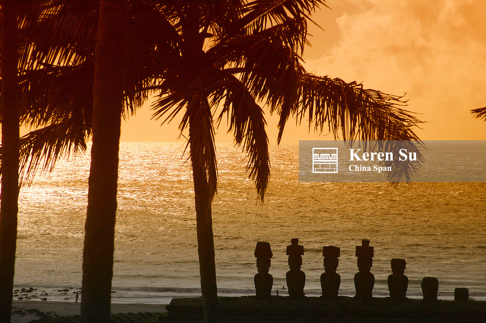 Silhouette of Seven Moais (volcanic stone sculptures) of Ahu Akivi and palm tree by the ocean, Easter Island, Chile