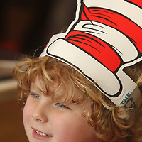 "London Tate, 5, of Tupelo, smiles as he listens to Tupelo Fire Departmant Captain Mark Patton, as he reads ""Go. Dog. Do!"" by Dr. Seuss Thursday afternoon at McDonald's on West Main Street in Tupelo as part of Dr. Seuss week."