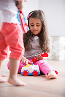 Cute girl dialing the toy telephone while playing with sister at home