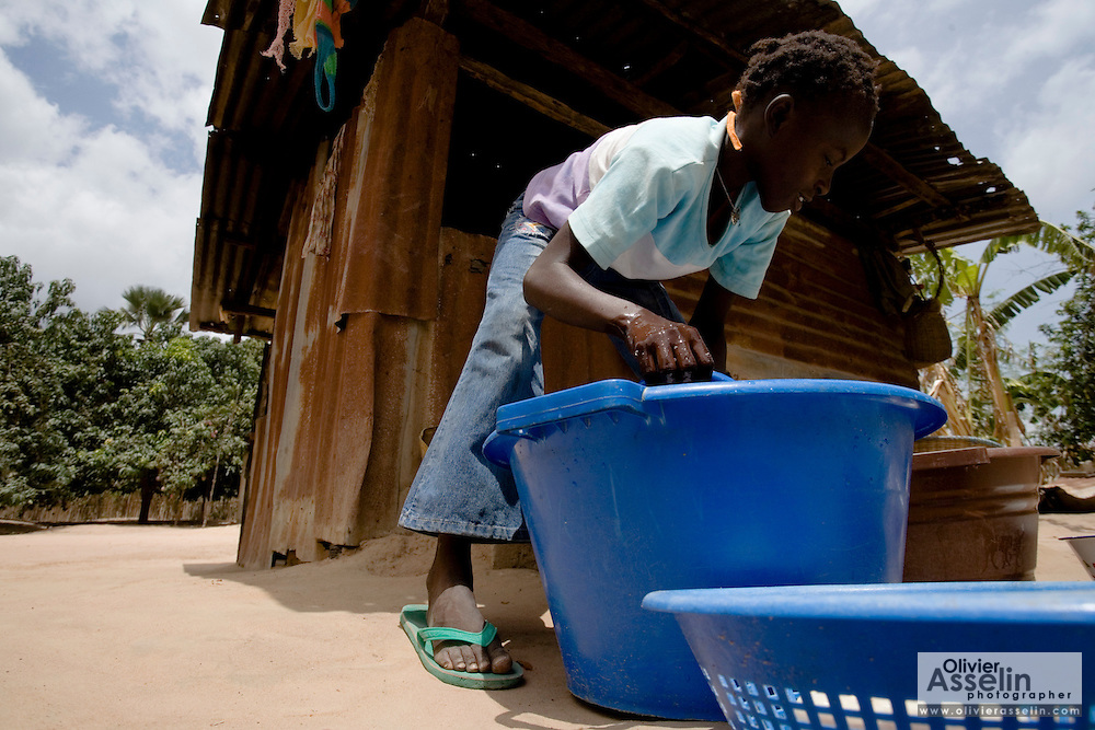 A girl cleans the dishes after coming home from school in the village of Essaout, Senegal, on Thursday June 14, 2007.