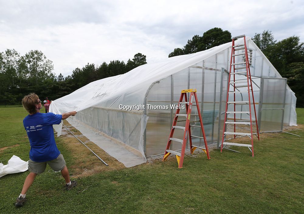 Zeke Dickey and other pull the plastic wrap tight before securing it to the new greenhouse under construction at Lawndale Elementary School Monday afternoon.