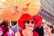 New York, NY - April 16, 2017. A woman in a large red hat under an orange parasol at New York's annual Easter Bonnet Parade and Festival on Fifth Avenue.
