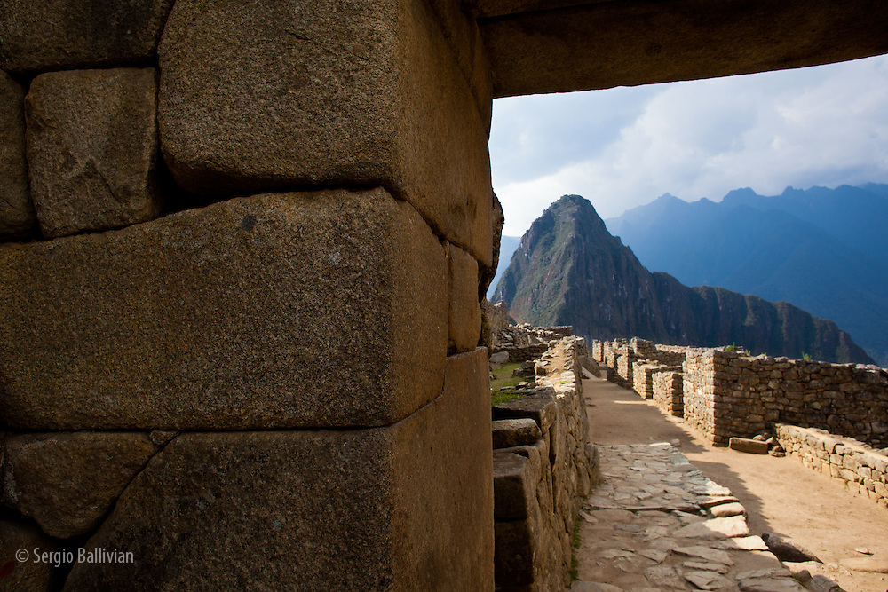 View of Machu Picchu - the Lost City of the Incas - located in the Vilcanota mountain range in south-central Peru.  Machu Picchu is a UNESCO site and is located on the steep jungle-covered slopes of this region.  The weather can change in minutes from clouds and rain to sunshine and warm temperatures. People can still trek to this city - three days away through the Vilcanota range.