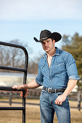 hot cowboy by a gate on a ranch