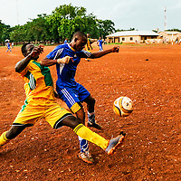 Players from opposing teams and different towns battle for ball possession during a game put on by the Nandom Youth for Peace and Development in Nandom, Ghana on July 8, 2016. The organization puts on games to bring community members together to promote peaceful elections in the upper west region of the country.
