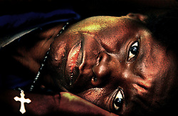A Malawian woman suffering from the HIV virus lies in her bed with a cross put on her by a relative at the Queen Elizabeth Hospital in Blantyre, Malawi, July 4, 2002.  In Malawi, as in several other affected countries,widespread poverty and the increasing economic and social disruption caused by a devastating HIV/AIDS crisis are additional factors disrupting agriculture and causing a growing food shortage which threatens 3.2 million people in Malawi -- 500,000 of which are already affected by the crisis.  The food crisis is part of a region-wide shortage affecting several countries in southern Africa, the result of a combination of harsh climatic conditions (droughts and flooding), poor management of food reserves and political and economic instability.