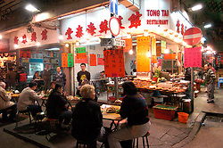 Night view of small street restaurant at famous Temple Street night market in Hong Kong