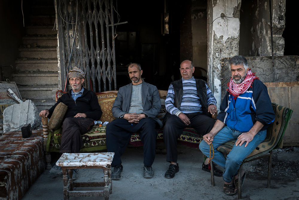 75-year-old Kasim Yahia Ali Hussein (left) sits with a group of men outside an abandoned building in Mosul's Old City. <br /> <br /> Like many homes in the old city, Kasim's house was hit by an airstrike, forcing him and his family to flee to a liberated area in the east of the city last July. He has since returned to the historic centre where he has taken on the role of guardian and gatekeeper, keeping watch 24 hours a day of his former neighbours' stores, warehouses and belongings.