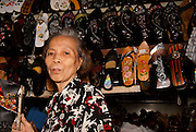 An elderly lady selling shoes in a stall in the Ben Thanh Markets, Saigon, Vietnam.