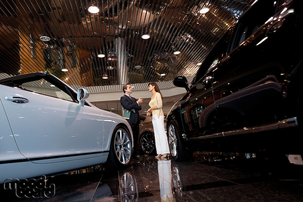 Salesman talking to woman in automobile showroom