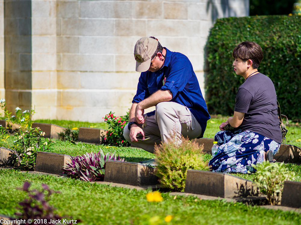 "11 NOVEMBER 2018 - KANCHANABURI, KANCHANABURI, THAILAND:  GARTH O'CONNELL, left from Australia, and his friend, SOKO TAMIKA, pray at the grave of O'Connell's great uncle, an Australian aboriginal soldier, killed working on the ""Death Railway"" and buried in the Kanchanaburi War Cemetery in Kanchanaburi, Thailand, during Rememberance Day observations. Kanchanaburi is the location of the infamous ""Bridge On the River Kwai"" and was known for the ""Death Railway"" built by Japan during World War II using allied, principally British, Australian and Dutch, prisoners of war as slave labor. There are 6,982 people buried in the cemetery, including 5,000 Commonwealth soldiers and 1,800 Dutch soldiers. November 11, 2018 marked the 100th anniversary of the end of World War I, celebrated as Rememberance Day in the UK and the Commonwealth and Veterans' Day in the US.    PHOTO BY JACK KURTZ"