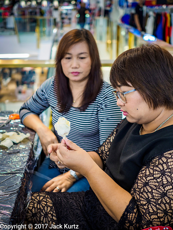 """24 MAY 2017 - BANGKOK, THAILAND: Women at the Emporium, an upscale shopping mall in Bangkok, make wooden roses to be used during the cremation of Bhumibol Adulyadej, the Late King of Thailand. In Thai culture it is customary to place wooden flowers in front of a deceased person's coffin or urn as a last tribute before cremation. The Royal Cremation Organisation Committee, which is overseeing plans for the cremation of Bhumibol Adulyadej, the Late King of Thailand, asked the Bangkok Metropolitan Administration (BMA) to provide three million wooden flowers for the late King's cremation. The BMA, in turn, has asked malls and civic organizations to provide flowers. The Mall Group, which owns Emporium, has pledged to provide up to one million wooden """"Wiangping"""" roses, which in Thai culture symbolize unconditional love. The late King will be cremated October 26, 2017.     PHOTO BY JACK KURTZ"""