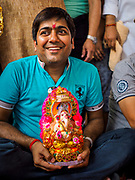 "23 SEPTEMBER 2018 - BANGKOK, THAILAND: A man holds small Ganesha statue at the Ganesha Festival at Wat Dan in Bangkok. Ganesha Chaturthi also known as Vinayaka Chaturthi, is the Hindu festival celebrated on the day of the re-birth of Lord Ganesha, the son of Shiva and Parvati. The festival, also known as Ganeshotsav (""festival of Ganesha"") is observed in the Hindu calendar month of Bhaadrapada, starting on the the fourth day of the waxing moon. The festival lasts for 10 days, ending on the fourteenth day of the waxing moon. Outside India, it is celebrated widely in Nepal and by Hindus in the United States, Canada, Mauritius, Singapore, Thailand, Cambodia, and Burma.    PHOTO BY JACK KURTZ"