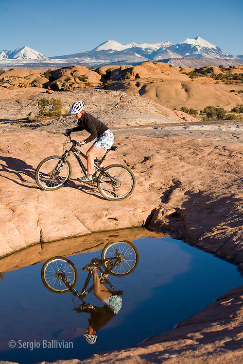A mountain biker rides around a puddle on the slickrock trail in Moab, Utah.