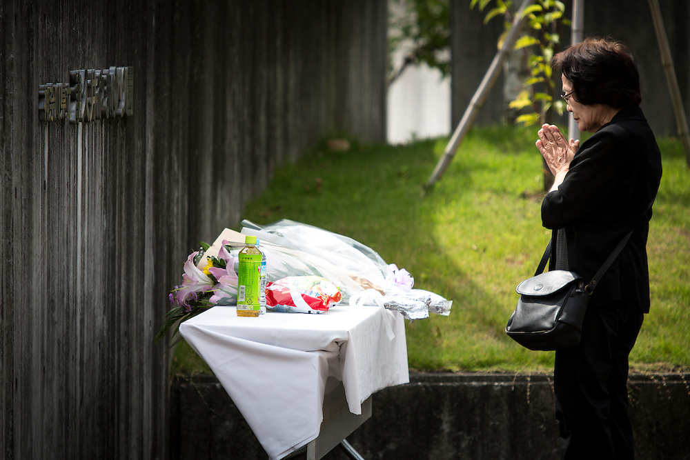 SAGAMIHARA, JAPAN - JULY 27 :  A relative pay respect after offering a flower for the victim in front of the entrance of Tsukui Yamayuri-en building at Sagamihara on Wednesday, July 27, 2016 in Kanagawa prefecture, Japan. Police arrested 26 year old Satoshi Uematsu after breaking inside the building facility for handicapped and killing 19 people and injuring 20 in the city of Sagamihara, west of Tokyo. (Photo: Richard Atrero de Guzman/NURPhoto)