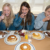 Karli Vaughn, 17, Whitney Webb, 15, and Courtney Carswell, 16, eat pancakes at the International house of Pancakes (IHOP) in Santa Monica during National Pancake Day on Tuesday February 28, 2012. National Pancake Day dates back several centuries to when the English prepped for fasting during Lent. Strict rules prohibited the eating of all dairy products during Lent, so pancakes were made to use up the supply of eggs, milk, butter and other dairy products, hence the name Pancake Tuesday, or Shrove Tuesday. IHOP served 4 million free pancakes on National Pancake Day . All of the free pancakes served on National Pancake Day  would have created a stack more than 31.5 miles high. Since the inception of National Pancake Day in 2006, IHOP has raised more than $5.35 million and given away more than 10.1 million pancakes to support charities in the communities in which it operates. National Pancake Day  is IHOP's largest one-day event in the company's 54-year history.