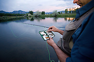 Man flyfishing on a lake near Boulder, Colorado at sunset.