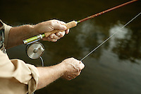 hands of a fly fisherman working a line on the water