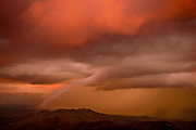 A storm passes at sunset to the east of the Santa Catalina Mountains near the San Pedro River, Sonoran Desert, Tucson, Arizona, USA.