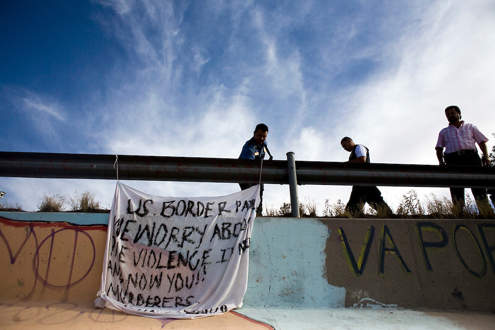 """Mexican Municipal Police from Juarez remove a banner that says """"US BORDER PATROL WE WORRY ABOUT VIOLENCE IN MEXICO AND NOW YOU!! MURDERERS.VIVA MEXICO."""" The banner was a protest against the killing of 15-year-old Sergio Adrian Hernandez Guereca, who was killed yesterday by a Border Patrol agent. The banner was hung on the Mexican side between the """"Puente Juarez"""" bridge and the """"Puente Negro"""" bridge."""