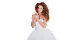 Portrait of beautiful young brunette in wedding dress with hands together over white background