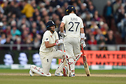 Joe Root of England is on on knee talking to Rory Burns of England after taking a blow in a delicate area off the bowling of Mitchell Starc of Australia during the International Test Match 2019, fourth test, day three match between England and Australia at Old Trafford, Manchester, England on 6 September 2019.