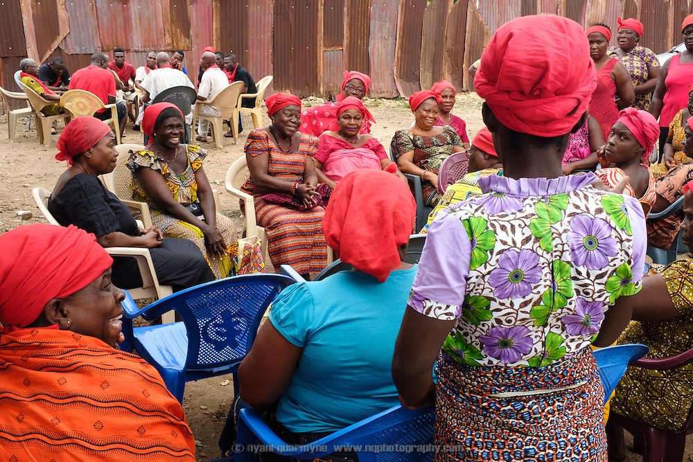 Mama Agblatsu III (fourth from left), a Queen Mother in Bankoe, a traditional division in the town of Ho in the Volta Region of Ghana, at a weekly early morning meeting of her clan. The clan is an important is an important part of the community's social fabric, and members meet weekly to discuss clan and family matters. After the main meeting, men and women break up into separate groups. The wearing of red signifies that the clan is in mourning - two of their number recently passed away, and funeral matters dominated the meeting.