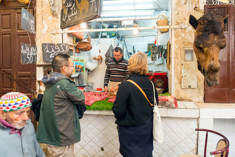FEZ, MOROCCO - 05th MARCH 2016 - Tourists chat with a butcher selling camel meat while grocery shopping the old Fez Medina, Middle Atlas Mountains, Morocco.