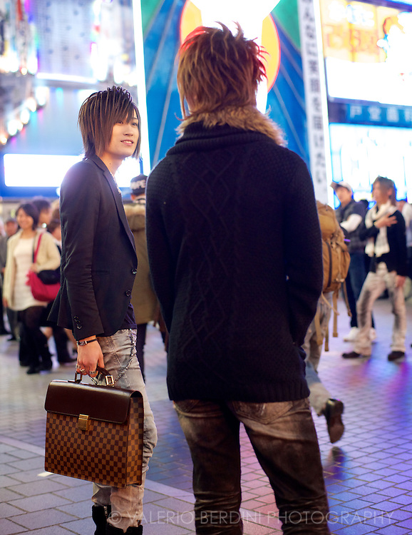 Two smart guys, with must-have Luis Vitton bags, stand chatting over 'pick-up' bridge. Osaka, Japan 2013