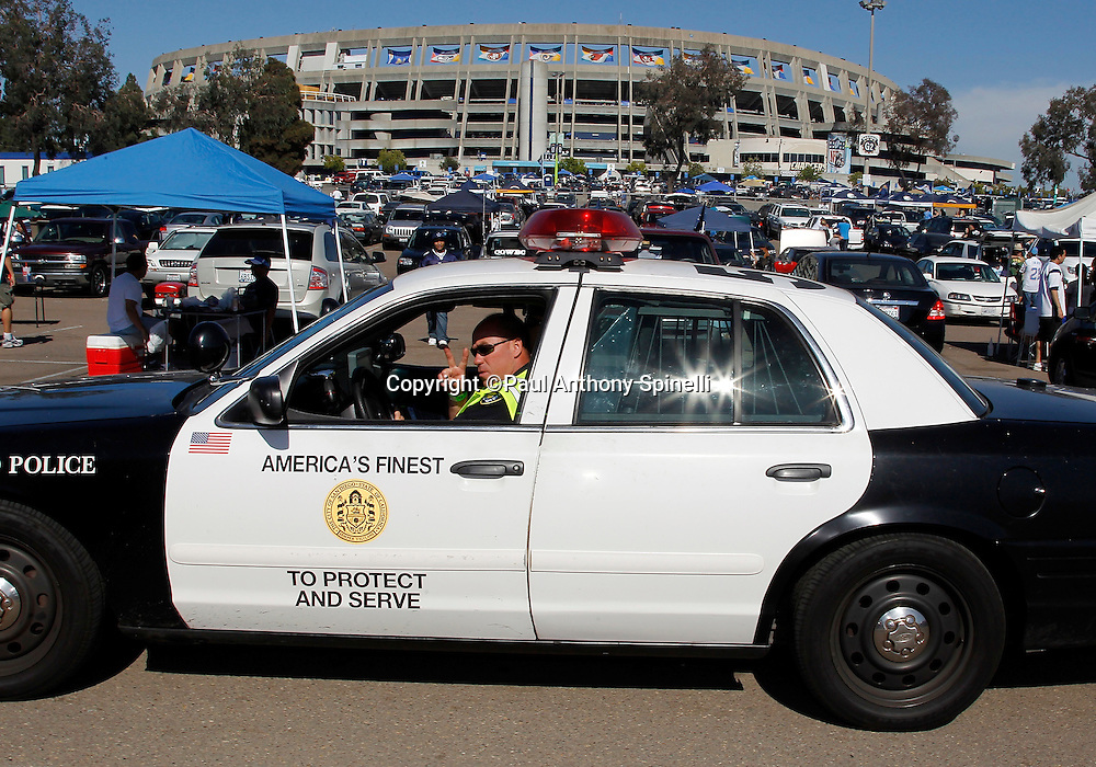 A Police Officer gives the victory sign as he patrols the parking lot while fans tailgate at the San Diego Chargers NFL week 2 preseason football game against the Dallas Cowboys on Saturday, August 21, 2010 in San Diego, California. The Cowboys won the game 16-14. (©Paul Anthony Spinelli)