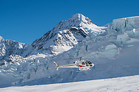 Helicopter coming in for landing on The Tasman Glacier (Haupapa) which is the largest glacier in New Zealand, and one of several large glaciers which flow south and east towards the Mackenzie Basin from the Southern Alps in New Zealand's South Island.