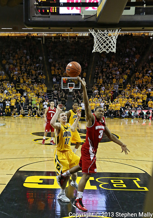 January 19 2013: Wisconsin Badgers guard George Marshall (3) puts up a shot as Iowa Hawkeyes guard Mike Gesell (10) looks on during the first half of the NCAA basketball game between the Wisconsin Badgers and the Iowa Hawkeyes at Carver-Hawkeye Arena in Iowa City, Iowa on Sautrday January 19 2013. Iowa defeated Wisconsin 70-66.