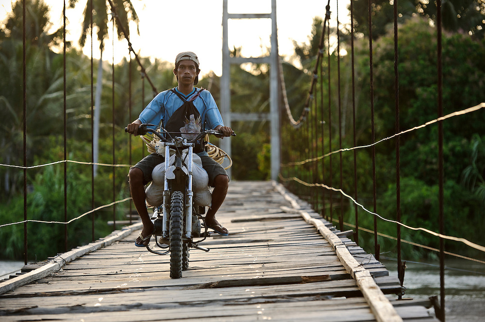 Farmers crossing a suspension bridge, Sausu Peore, Central Sulawesi, Sulawesi, Indonesia.