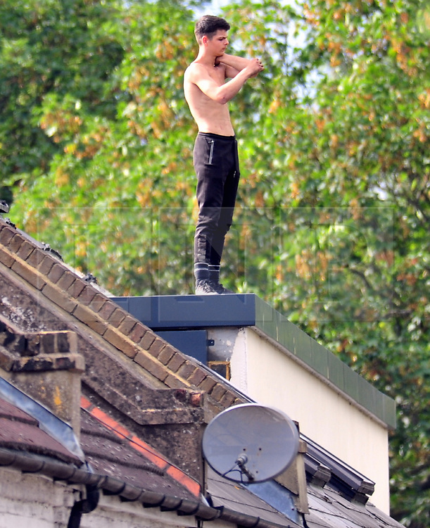 © Licensed to London News Pictures. 20/08/2018<br /> ERITH, UK.<br /> West Street in Erith is closed by police due to a teenage boy on the roof of houses. Police negotiators have been on scene all day trying to get the boy down. The male is believed to be 17 years old.<br /> Photo credit: Grant Falvey/LNP