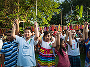 10 SEPTEMBER 2016 - BANGKOK, THAILAND: Children raise their hands above their heads to show solidarity with the community's decision to stay in Pom Mahakan. Forty-four families still live in the Pom Mahakan Fort community. The city of Bangkok has given them provisional permission to stay, but city officials say the permission could be rescinded and the city go ahead with the evictions. The residents of the historic fort have barricaded most of the gates into the fort and are joined every day by community activists from around Bangkok who support their efforts to stay.                PHOTO BY JACK KURTZ