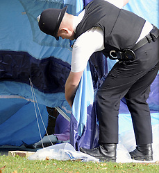 © Licensed to London News Pictures. 10/10/2011. London, UK. ** Image shows part of the murder victims body** A Police officer stands over the forensics tent covering the body of a woman killed in a stabbing in Bexleyheath, South London today (10/10/2011). Photo credit : Grant Falvey/LNP