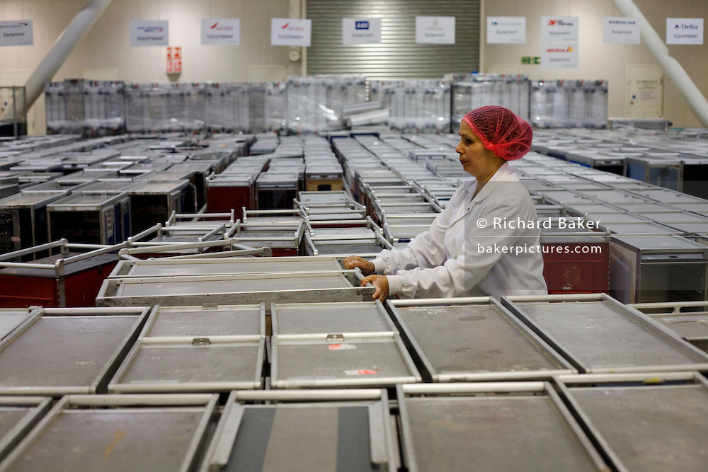 "A lady employee of the world's largest independent provider of airline catering and provisioning services, Gate Gourmet, wheels a galley trolley to be filled with fresh airline food in the company's factory on the southern perimeter road at Heathrow Airport, West London. Gate Gourmet serve more than 200 million meals on 2 million airline flights a year to their 250-plus airline customers at more than 100 airport locations around the globe. Apart from creating the bespoke meals for an airline's culture and ethnic demands, that pack the pre-flight carts, deliver and load into the aircraft galleys and afterwards, they dispose of the waste and strip, wash and sterilize the equipment. From writer Alain de Botton's book project ""A Week at the Airport: A Heathrow Diary"" (2009). ."