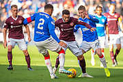 Jake Mulraney (#11) of Heart of Midlothian FC is closed down by James Tavernier (#2) of Rangers FC and Steven Davis (#10) of Rangers FC during the Ladbrokes Scottish Premiership match between Heart of Midlothian and Rangers FC at Tynecastle Park, Edinburgh, Scotland on 20 October 2019.