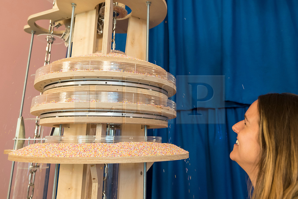 "© Licensed to London News Pictures. 03/07/2018. LONDON, UK. A staff member views a hundreds and thousands machine at a preview of ""SCOOP: A Wonderful Ice Cream World"", the first official exhibition of the British Museum of Food.  The exhibition presents items from the Robin and Caroline Weir Collection and explores the science and appeal of ice cream going back 400 years.  The exhibition takes place at the Gasholders near Granary Square in Kings Cross and runs 3 July to 30 September 2018.  Photo credit: Stephen Chung/LNP"