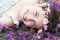 Smiling Pre-teen girl with flower headdress lying in field of flowers close-up