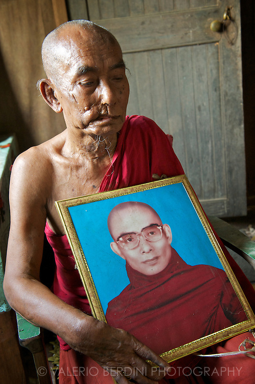 82 years old monk who suffered the consequences of a motorbike accident that costed him the amputation of the left arm and several physical problems. He asked to pose with a portrait of his young self.