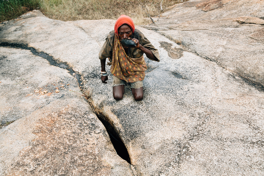 Piwa, a septuagenarian of the Hazda tribe,  stops to take water from a natural spring whilst out hunting in the Yaeda valley area in Northern Tanzania. Photo by Greg Funnell, March 2016.