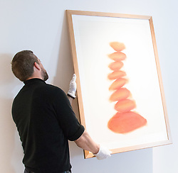 "Christies, St James, London, March 4th 2016. A gallery technician hangs David Nash's ""Column"", pastel on paper, created especially for the auction at the preview for the It's Our World charity auction at Christie's. Over 40 leading artists including David Hockney, Sir Antony Gormley, David Nash, Sir Peter Blake, Yinka Shonibare, Sir Quentin Blake, Emily Young and Maggi Hambling have committed artworks to the It's Our World Auction in support of The Big Draw and Jupiter Artland Foundation, to be sold at Christie's London on 10 March 2016."