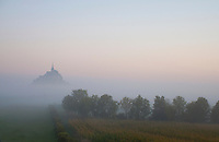 The island of Mont St. Michel rising out of the mists at dawn.