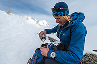 Squash Falconer, a female British adventurer, as seen pouring warm tea on a snowy ridge of Aiguilles Marbrées on a cold and cloudy Winter afternoon in Mont Blanc Massif.