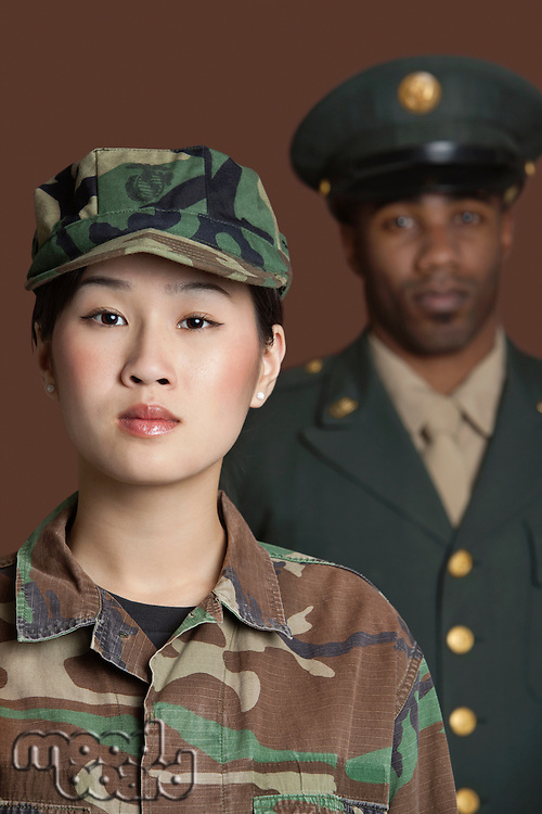 Portrait of young female US Marine Corps soldier with officer in the background